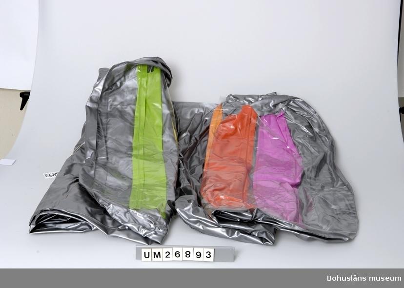 """410 Mått/Vikt L 197 B 93 CM (OUPPBLÅST)) 433 Teknik 1 SVETSAT IHOP Uppblåsbar luftmadrass av plast (PVC?). Silvergrå undersida med vävmönstrad yta, genomskinlig plast som ovansida, invändiga mellanväggar på tvären (mellan de olika """"luftrummen"""" som bildas när man blåser upp madrassen) i klara färger: vit-tonad blåröd (ceriserosa), två olika gulröda (orange), gult och ljusgrönt (ärtgrönt). En genomskinlig plastventil med fastsatt lock på varje kortsida. Vid ena kortsidan en extra u-formad luftkudde (ryggstöd?) fastsvetsad ovanpå madrassen, allra överst ytterligare en liten kudde (nackkudde?). På den lilla kudden tryckt text i blått: """"610 """"FLOTATION TOY WARNING USE ONLY UNDER COMPETENT SUPERVISION"""", därunder varningstext på 14 andra språk, varav ett svenska: """"VARNING ANVÄND EN- DAST UNDER VUXENS ÖVERINSEENDE"""". Lite smutsig på undersidan bl. a. oljefläckar.  Anders har fått luftmadrassen i födelsedagspresent i juni -98 av kompisar. Använd i vattnet som badmadrass bara någon gång sommaren 1998, eftersom det inte var så bra badväder den säsongen. Det var kallt i vattnet och mycket brännmaneter. Se Tillstånd & Vård.  Insamlad i samband med SAMDOK-dokumentation av båtturism. För mer   uppgifter om brukaren och dokumentationen se UM26869."""