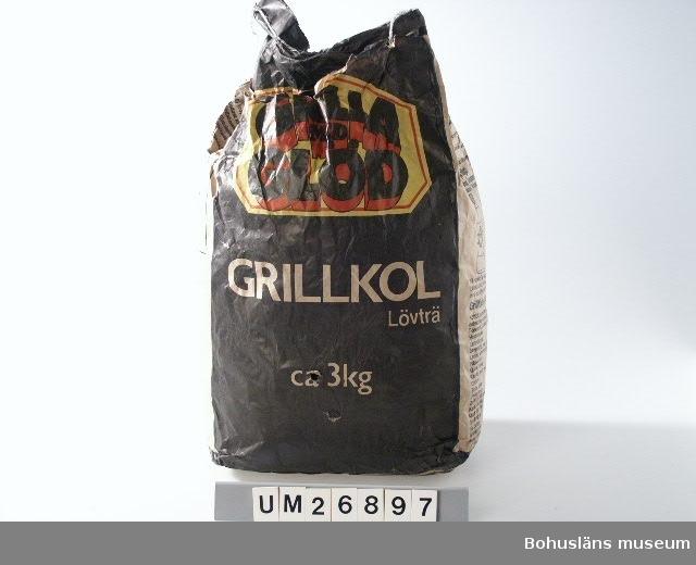 """Svarta grillkolsbitar av lövträ. Förvaras i två påsar utanpå varandra. Den inre är en brunbeige papperspåse med tryckt text (och bilder) i svart, rött och gult. Det är påsen som kolet förvarats i vid försäljning. Påsen är öppnad upptill (uppriven). På påsens långsidor finns tryckt text: """"GRILLA MED GLÖD GRILLKOL Lövträ ca 3 kg"""". På ena kortsidan texter under rubrikerna: """"Vad lämpar sig att grilla?"""" """"Grilla miljövänligt!"""" (därunder finns även bild av Änglamark tändvätska och tändpapper, ur Kooperativa Förbundets serie milövänliga varor, vid 1990-talets slut sålda på Konsum, Domus och OBS) """"Grilltider ungefärliga"""". På andra kortsidan produktinformation, varningstext (mot eldfara) och prismärkning genom streckkodsmärkning. Den yttre påsen är av vit plast med affären Intersports tryck i svart, rött, blått. Handtagshål finns nära ovankanten på ena långsidan, på motsatta sidan är en knut knuten precis över handtaget. Små smutsfläckar på yttre plastpåsen.  Anders förvarade sitt grillkol på detta sätt i dubbla påsar dels för att inte kolet skulle smutsa ner och dels för att det inte skulle bli  fuktigt under seglingen. Hans grill och dess förvaringslåda är också insamlade och inmärkta som UM26896.  Insamlade i samband med SAMDOK-dokumentation av båtturism.  För fler uppgifter om brukaren och dokumentationen se UM026869"""