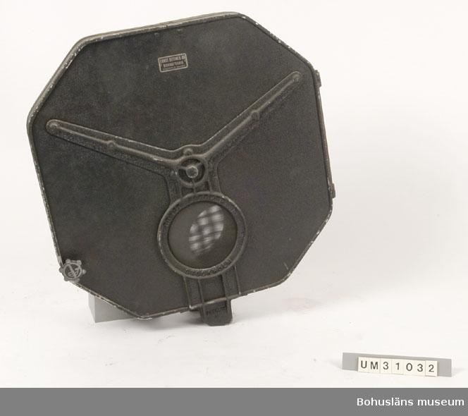Åttkantigt delbart filmhus av svart brännlackerad metallplåt. Har använt tillsammans med projektor UM31031 och är av samma typ som det filmhus som sitter monterat på filmprojektorn.  Projektorn är tillverkad av AEG på 1920-talet och har använts i Folkets Hus i Sjöbol vid Lysekil.  Till projektorn hör en lång rad delar och olika tillbehör, UM31031 - UM31062.  För ytterligare upplysningar om filmprojektorn, dess olika delar och användning, se UM31031.