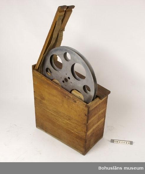 Rektangulär trälår av ek med sluttande överdel. Sinkade hörnen. Invändigt fyra separata fack för filmrullar och tomma spolar. Separata lock över varje fack, fästade med gångjärn. När man lyfter locket lyfts filmspolen behändigt  upp på ett band  av sadelgjord.  På ovansidan märkt med en liten metallskylt med texten:  ERNST DITTMER A.B. BIOGRARTEKNIK STOCKHOLH (Sweden)  Innehåller två tomma filmspolar, UM31039 samt en likadan, omärkt spole.  Uppgifter ur Wikipedia 2006, http://sv.wikipedia.org/wiki/Ernst_Dittmer Ernst Dittmer född Ernst Gustav Vilhelm Dittmer 28 april 1890 i Göteborg död 17 februari 1941, svensk fotograf. Dittmer var anställd som fotografmedhjälpare i Jönköping under fyra år, fotograf vid Svenska Biografteatern AB i Kristianstad 1908-1909, fotograf och teknisk ledare vid Svensk Teater Konstfilm i Malmö 1910-1912, han drev det egna bolaget Rekord-Film i Köpenhamn 1912-1917 samt teknisk direktör vid Alhambra Film A/S.  Trälåren har använts tillsammans med projektor UM31031.  Projektorn är tillverkad av AEG på 1920-talet och har använts i Folkets Hus i Sjöbol vid Lysekil.  Till projektorn hör en lång rad delar och olika tillbehör, UM31031 - UM31062.  För ytterligare upplysningar om filmprojektorn, dess olika delar och användning, se UM31031.