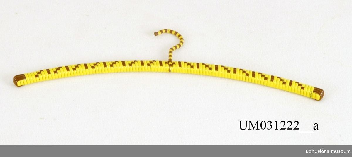Plastklädd smal trägalge lindad med kraftig gul och brun  plastrem i dekorativt mönster, UM031222:1 och UM031222:2. 1970-tal.