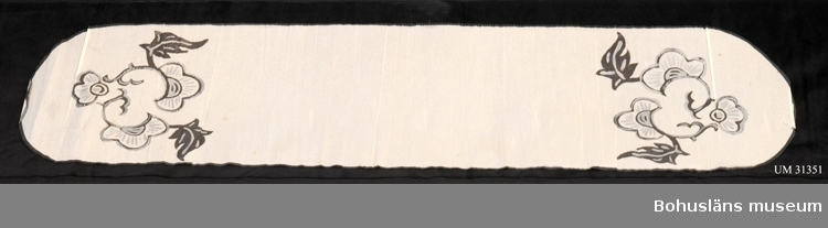 Oval duk av kräppat vitt papper. Svart målad dekorkant, i ändarna målade blommor och blad  i svart och silver i rokokliknande mönster. Duken har använts på en begravning i brukarens barndomshem på gården Torp i Uddevalla kommun. Duken är troligen inte hemtillverkad utan köpt. Det var en grannfamilj som bad att få hyra in sig hos familjen Johansson för begravningen av en av sina föräldrar. De bodde själva så trångt.  Brukaren var 15 år vid detta tillfälle och minns hur hon och en av grannfamiljens döttrar  dekorerade bordet i salen. Man klippte 8-10 cm breda remsor av svart och vitt kräpp-papper. Remsorna snoddes om varandra och fästes utmed bordskanten med nålar i den vita bordsduken. Mitt på bordet låg pappersduken.  Grannfamiljen, tre ogifta syskon, ordnade med begravningsmaten. En kokerska, Fina, kom från stan (Uddevalla) en dag i förväg och förberedde maten, trillade köttbullar mm. Klockan nio anlände begravningsgästerna och fick kaffe. Efter begravningen återkom sällskapet och åt middag, bland annat av stek, grönsaker, sås och potatis. Även äggost och andra ostar serverades. Även allt kaffebröd var hembakat. Två flickor hjälpte till med serveringen. Gården Torp 1:26 var den minsta på orten, ett hemman om 5 ha samt skog. Familjen hade två barn, fyra kor, häst och höns. Fadern fiskade en del för att dryga ut mathållningen. Gården är riven och idag ligger trafikapparaten vid Torps Köpcentrum på delar av de  gamla ägorna.   Ägaren har senare varit i kontakt med andra äldre grannar för att höra om någon känner igen denna typ av duk. Ingen av dessa hade använt en sådan duk under 1940-talet i Herrestad. Därför menar givaren att duken snarare kan ha använts på hennes morfars begravning 1935. Han hette August Johansson, född 1851, och var bonde på gården Myren under Herrestad prästgård.