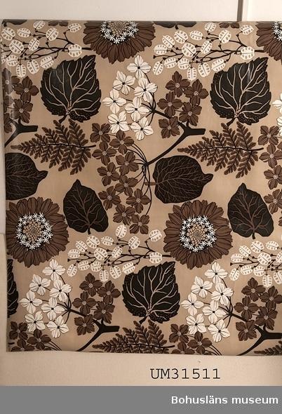 Rektangulär plastduk av PVC-skikt på bomullsväv från 1970-talet. Blommönster; kraftigt floralt mönster av stora blad och blommor i två nyanser av brunt och vitt mot en beige botten.  Ytterligare en plastduk, UM031510, från 1960-talet, är insamlad från samma hem.  Duken har använts till matbordet i allrummet i en  sommarstuga i Sundsandvik, Bohuslän. Duken var avpassad för bordet i utdraget skick. I allrummet finns panoramafönster mot fjorden, på motsatt vägg ett högt placerat långsmalt fönster,  en murad öppen spis, lackat trägolv med smala plank, vita väggar och tak. För interiörfoto, se UMFA55058.  Föremålet har använts av familjen Abrahamson i deras sommarstuga i Sundsandvik, byggd 1939. För ytterligare upplysningar om förvärvet, se UM031385.