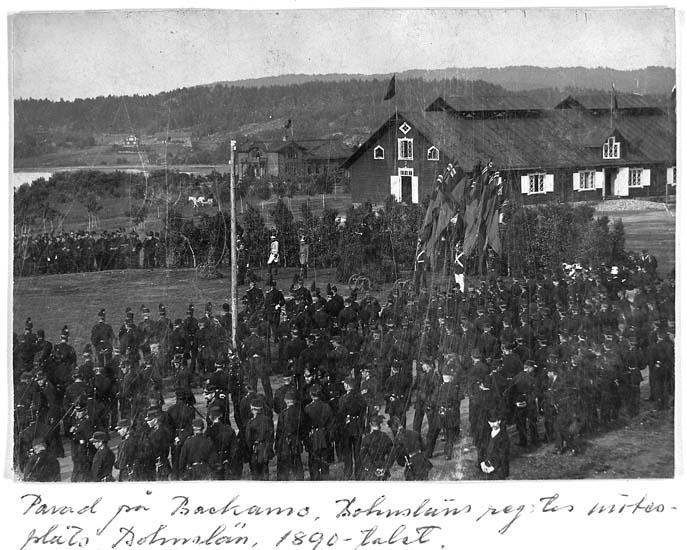 """Text på kortet: """"Parad på Backamo, Bohusläns reg:es mötesplats. Bohuslän, 1890-talet""""."""