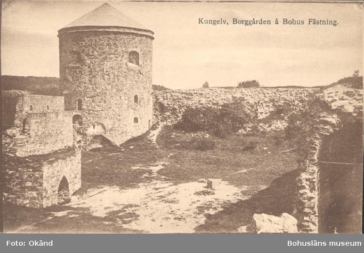 """Tryckt text på kortet: """"Kungelv. Borggården å Bohus Fästning"""". """"Förlag: P. G. Bergh, Kungelv""""."""