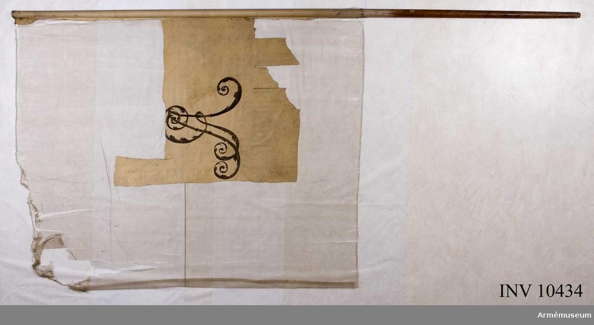Grupp B.  Fanduk av vit kypert varå broderat i guld omvänt lika å båda sidor, i mitten Gustav IV Adolfs namnchiffer GA under sluten kunglig krona, med ytter- och innerfoder i rött silke samt stenar i olikfärgat silke, allt 52 cm högt. I hörnen slutna kungliga kronor liknande namnchiffrets, kantad med vitt sidenband, fäst med vitt sidenband och förgyllda spikar.  Stång 299 cm, Höjd, bandet på stången, 167 cm.