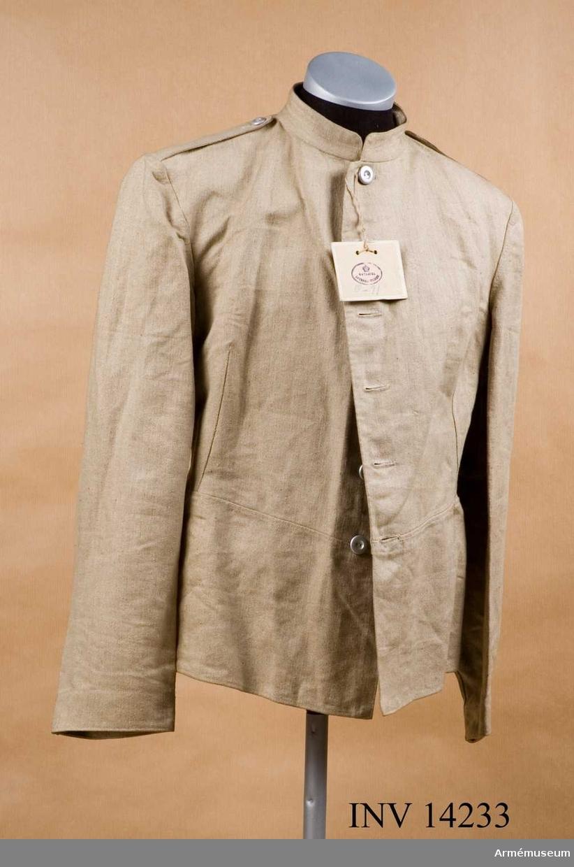 """Grupp C I. Lägerrock, da. Drejlsfrakke, av grovt linne, 60 cm lång, åtsittande med tvärsöm i midjan. Rocken är enradig med 6 knappar. Axelklaffar av samma linne, 14 cm lång och 3,5 cm bred. Axelklaffarna fastsydda vid ärmsömmarna och fästade vid rocken med knappar. Foder saknas, men på vänstra sidan finns en inre ficka. Det finns stämpel """"1914"""", """"PRM"""" - Prövemaessigt - modellenligt. Munderingsvaesent i Fredstid. 1:sta Haefte, Kjöbenhavn 1908 sid 30 paragraf 54. Stempling. Knappar av vit metall, 2 cm i diam, 6 st på bröstet, 2 st på axelklaffar och 2 st på skörten i midjan. Krage upprättstående, 3 cm hög. Rocken har pappersetikett, på vilken det står på ena sidan """"Materiel, Intendenturen"""" med kronan ovanpå. På andra sidan """"Drejlsfrakkje, prove 1907"""", """"ankom den 20.2.1914""""./ Granberg 1952."""