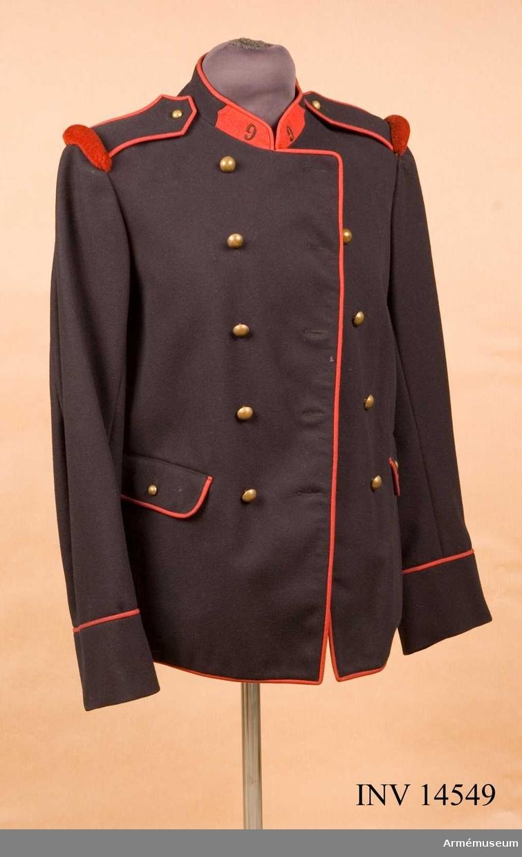 """Grupp C I.  Vapenrock för menig vid 9. infanterireg:t Av mörkblått kläde. Tvåradig med 5 knappar i rad. Åtsittande. På bakre skörten, två falska fickor kantade med röd passpoal, vardera med 2 knappar. Skörten öppna, l:210 mm. På V sida finns fastsydd järnring för bajonetten.   Axelklaffar av mörkblått kläde med röda passpoaler runt; fastsydda vid ärmsömmarna, som äro fästade vid rocken med knappar. Vid ärmsömmen finns axelvulst av rött ylle.   Fickorna två, på sidan, försedda med lock kantade med röd passpoal och två knappar.   Foder av grått bomullstyg. Knappar halvkullriga, av gulmetall, d:20 mm. Tio st i två rader på bröstet, 4 st. på skörten: d:10 mm; 2 st på axelklaffarna och 2 på fickorna.   Krage öppen ståndkrage - snedskuren av samma mörkblå kläde, vardera försedd med röd klaff; på klafferna finns broderade i svart regementets nummer """"9"""", röd passpoal runt kragen och framtill från magen ända ned. Kragen stänges med hyska och hake.   Ärmuppslag rakskurna, h:90 mm, med röd passpoal på uppslagets överkant."""