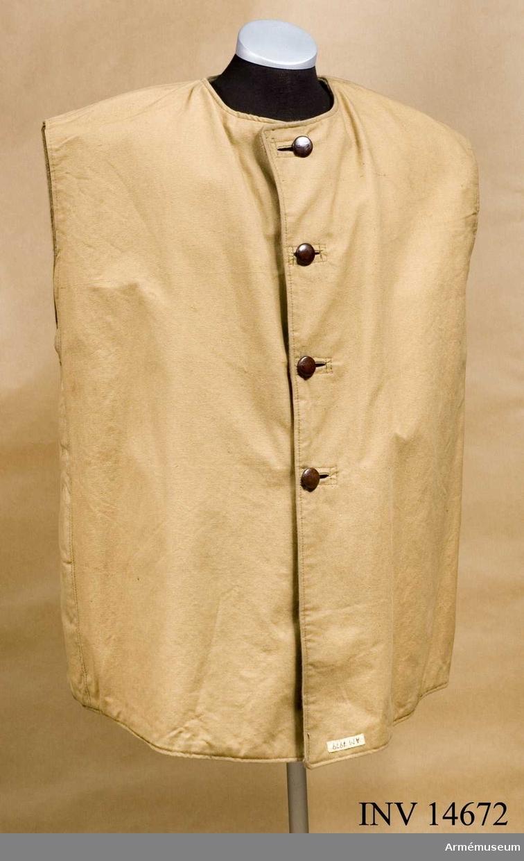 """Grupp C I. ÖVERROCK av brunt presenningstyg, breda, med en knapprad (fyra knappar). Foder av varmt ylletyg med stämpel """"2"""" (storlek). Knappar, bruna, 25 mm i diameter, som fasthålles vid rocken med ringar. Krage och ärmar saknas. Överrocken användes under den kalla årstiden och över en vanlig överrock."""