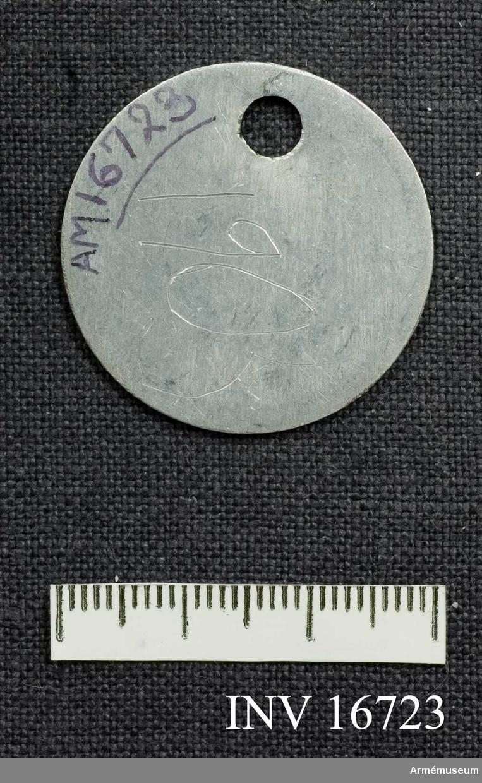 En rund bricka med ett stansat hål upptill för en kedja. Ingraverat står det: I 1 Fanj. Malmsten 1905.