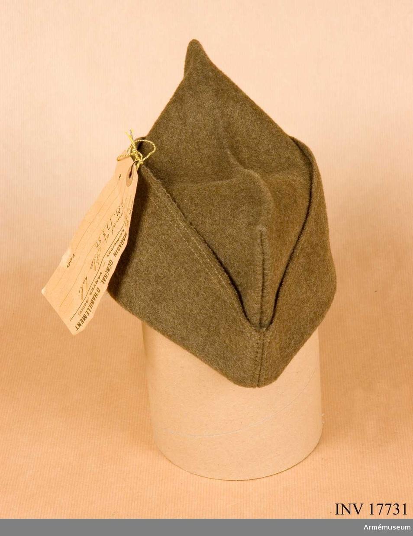 """Grupp C I. Ur uniform m/1935 för manskap, Frankrike: rock, ridbyxa skjorta, halsduk, benlindor, kappa, skor, hjälm, mössa, ränsel, kokkärl, flaska, brödpåse, livrem, gasmask. På franska bonnet de police. Fyrkantig båtmodell av kakifärgat kläde med svettrem av gult tyg med många stämplar: """"T 55"""", """"16.10.1935"""", """"Commision de réception"""" """"...(oläsligt) Paris"""". Pappersetikett med text """"Envoi du Magasin General d'habittement, 7 Rue Larmeraux Vanves (Seine)"""". """"Bonnet de Police khaki"""".  LITT  Handbuch der Uniformenkunde, Prof. R Knötel, Hamburg 1937. Denna fältmössa av båtmodell infördes i franska armén år 1915. Den var då blågrå, men fick år 1935, liksom uniformen, khakifärg. Les uniformes de l'armée Francaise ,terre, mer, air. Texte du Commendant E-L Bucquoy, Paris 1935, sida 7: """"Bonne police"""", kort beskrivning och bild. Enl kapten W Granberg."""