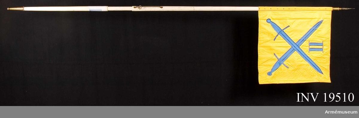 """Kommandotecknet är maskinsytt. Det är dubbelsidigt med gul botten i sidenkypert. I mitten av duken på båda sidor finns motiv av intarsia  med två korslagda svärd. Ovanför svärden finns en romersk tvåa även den i intarsia. Duken är spikad i tre rader om vardera 13 tännlikor i varje rad. Duken är vid stången klädd med sidenrips. Stången är vitmålad av typ standarstång som  ej är delbar. På doppskon texten """"Andra Militärområdet"""".   Samhörande nr är AM 19511-12. Standar, kommandotecken."""