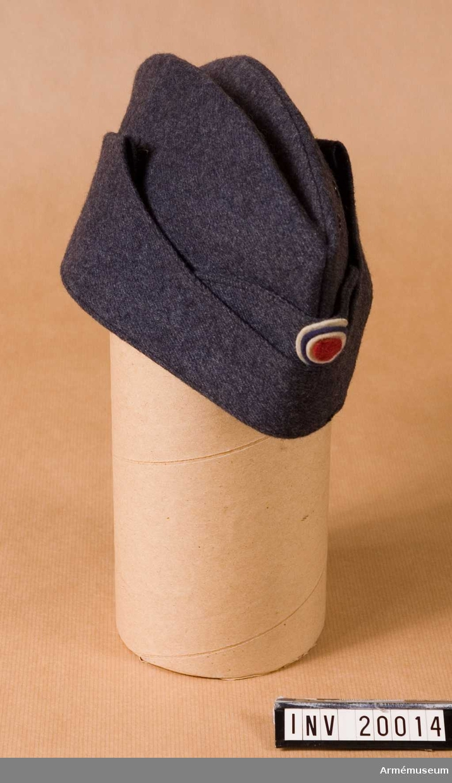 """Grupp C I. Samhörande är ,rock, byxa, skjorta, slips, mössa, skor. Lägermössa. Ur uniform 1943 för manskap vid infanteriet i Norge. Av blågrått färgat kläde, båtmodell. På mössans framsida finns norska nationalkokarden av kläde i norska färgerna, röd/vit/blå/vit. Två hål för ventilation. Foder av svart bomullstyg med svettrem av grått tyg med  fastsydd vit lapp med text """"1941"""" - """"7 1/4"""" (storlek) """"H. 631642/ 41/ 01"""" (truppbenämningen)."""