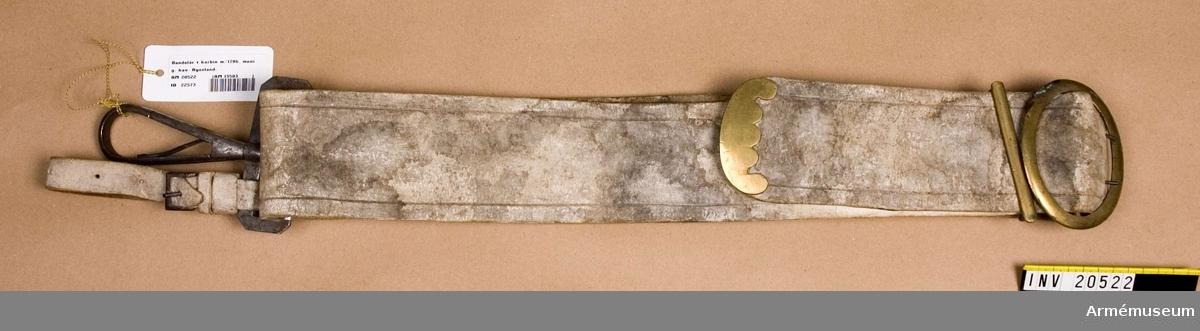"""Grupp C I. Karbinbantlär av vitt """"lossin""""-läder, med ovala spännen, speciallöpare och beslag på änden, allt av mässing. En karbinhake.  Remmen har pressad kant. Beslagen har på baksidan öglor med hål, som fäste beslagen vid remmen. På karbinhaken en smal rem av lossin-skinn med spännen, troligen använd till att koppla fast karbinen med. LITT  F von Stein, Ceschichte den russischen Heeres, Hannover 1885. sida 181: Enl. dagorder 10 april 1786 fingo lätta ridande regemente bära sina karbiner på bandolär med krokar. J Eletz, Cradnohusarens historia. S. Petersburg, 1890. sida 391: Enl. dagorder 17 juni 1826 kostade bandolärremmmen med alla mässingsdelar och järnkrokar 5 rubel och 48 kop."""