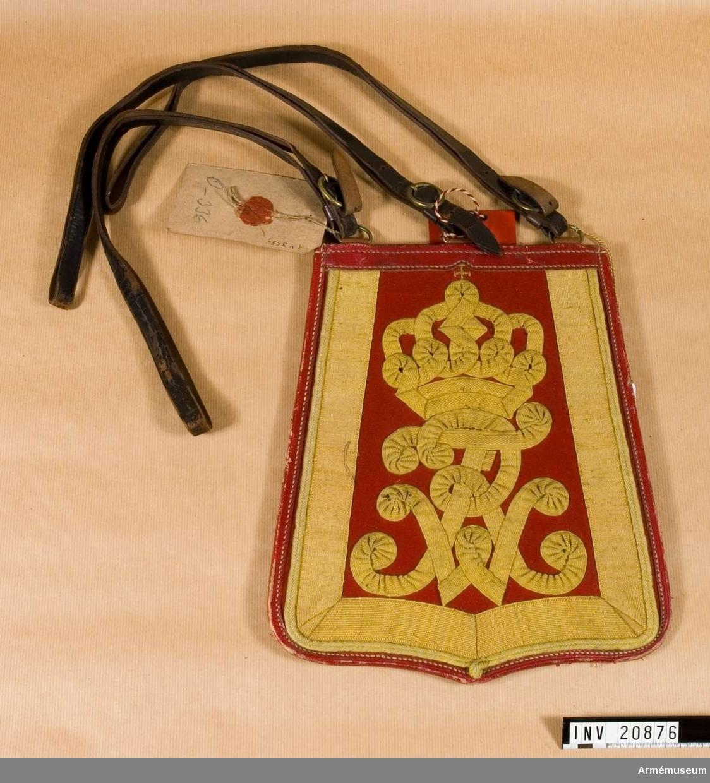 """Grupp C.  Har ett fodral av svart läder med lock som stängs med en läderknapp. Locket är av svart läder och kantat med rött läder. Längs sidorna och nedre kanten är locket täckt med ett gult 3 cm brett band av bomull. I mitten av locket konungens  namnchiffer """"F.V.R."""" Fredricus Wilhelms Rex med krona -allt av gult bomullsband för namnchiffret av 1,5 cm:s bredd och för  kronan av 1 cm:s bredd. Tre bärremmar av svart läder med  ringar och spännen av mässing.  Sebeltaskan har en pappersetikett med påskrift: """"Sabeltasche für Husaren, Berlin den 5. Januar 1876.  Miliair-Oeconomindepartement. Abteilung für die Bekleidung Angelegenheiten,"""" Underskrift- ad. No 104/1 Mod. 3 H 17.  På andra sidan av etiketten ett rött sigill med tyska örnen och oläslig påskrift."""