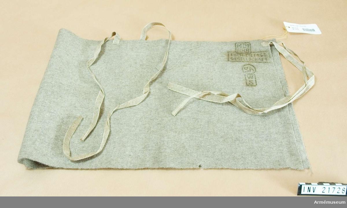 """Grupp C I. Tyska Leibbinde"""". Av grå-brunt fårylle kläde. Två par band av bomullsgarn för att binda fast gördel om magen. På gördelns baksida finns stämplar: """"M.D.1"""" = Monoturs depot 1. """"888"""" = år 1888. """"Tuch-lieferung Gesellschaft"""". """"S.A."""", """"W.S."""""""