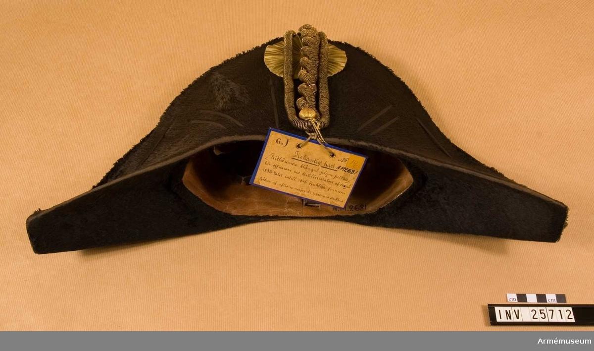 Grupp C I. Trekantig hatt. För artilleriofficerare; 1830.45. Har burits av givarens far, f.d. majoren tygmästaren och artilleristabsofficeren C A Westman. Blå och gul fjäderplym fattas.