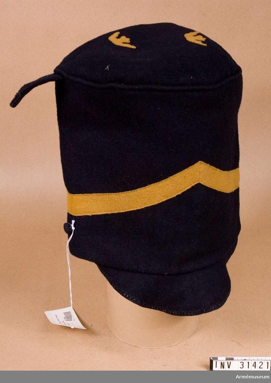 Grupp C I.  Ur uniform för manskap vid Livregementets dragonkår; 1815-1823. Består av kollett, ägiljett, byxor, skärp, mössa, tschakå, plym, kordong, pompong, vapenplåt, fjällband, knapp, knapp, sölja, halsduk, kartusch, kartuschrem, sabeltaska, rem t sabeltaska, koppel, handrem, stövlar, sporrar.  Mössa av blått kläde med tre kronor av gult kläde på mösskullen.