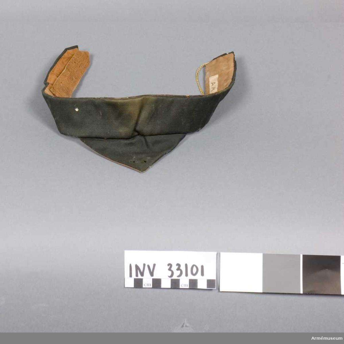 Grupp C I.  Hlasduk av svart yllekypert. Foder av linne med två stycken svarta stämplar. En tunn läderkant i överkant. Läderstropp av svart spänne för knäppning.