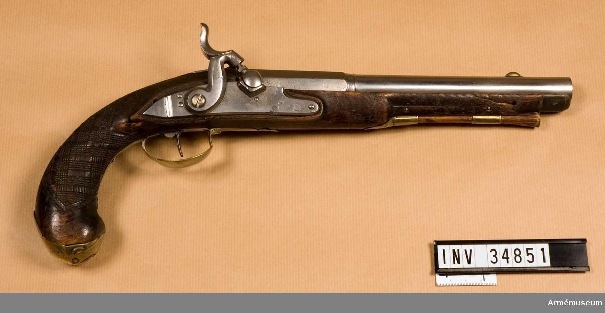 Grupp E III.  Pistol med slaglås. Ändrad från flintlås.  Pipa med åttkantigt kammarstrycke, beslag av mässing och laddstock av trä.   På kolvhalsen ett skuret rutmönster som antagligen inte är ursprungligt.