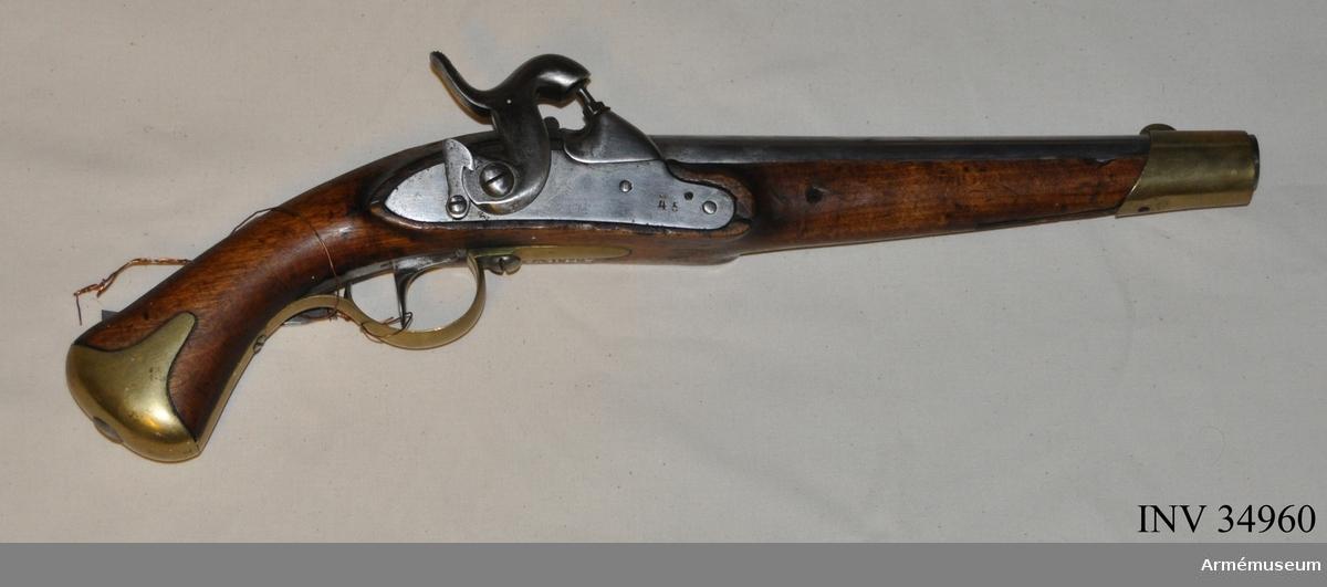 """Grupp E III c. Tappstudsarepistol m/1820-57 med slaglås. Antal räfflor: 4 st. Räffelstigning: Ett halvt varv på piplängden. Spetskulans längd 23 mm, Spetskulans diameter 15,44 mm. Spetskulans vikt 25,88 g. Krutladdningens vikt 3,31 g. Med undantag av att pistolen är mera nött, överensstämmer vapnet helt med AM 1932:4849. På pipans undersida till höger är instansat 486, på vänster däremot APN. På pipans översida längst bak finns numret 45 och flera bokstäver däribland ett krönt Ch, vilket väl anger att vapnet ändrats från flint- till slaglås samt försetts med tapp i Christianstads gevärsförråd. Dylika ändringar utfördes nämligen, liksom andra reparationer, vid gevärsförråden Stockholm, Karlsborg, Kristianstad och Visby (Jochnick, """"Handgevärslära"""" 1854, sida 4.) På låsbleckets utsida 45 angivet, på insidan APN. På stocken vänstra sida bakom låset samt på sidbleckets utsida står numret 45. På insidan av näsbandet och sidblecket sitter en stämpel med ett N. Framtill på kappan är numret 729 inslaget. Se övrigt AM 1932:4849. Laddningsförhållande enligt Jochnick """"Handgevärslära"""" 1863, sidan 61, vilken uppgift dock egentligen rör pistoler m/1820-49. Jochnik omnämner ej ovan beskrivna modell. Pistolen är i par med AM 34959. J Alm."""