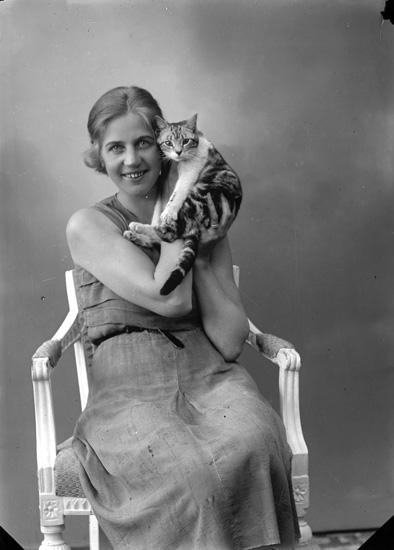 """Enligt fotografens journal nr 6 1930-1943: """"Adolfsson, Fru (med katt)""""."""