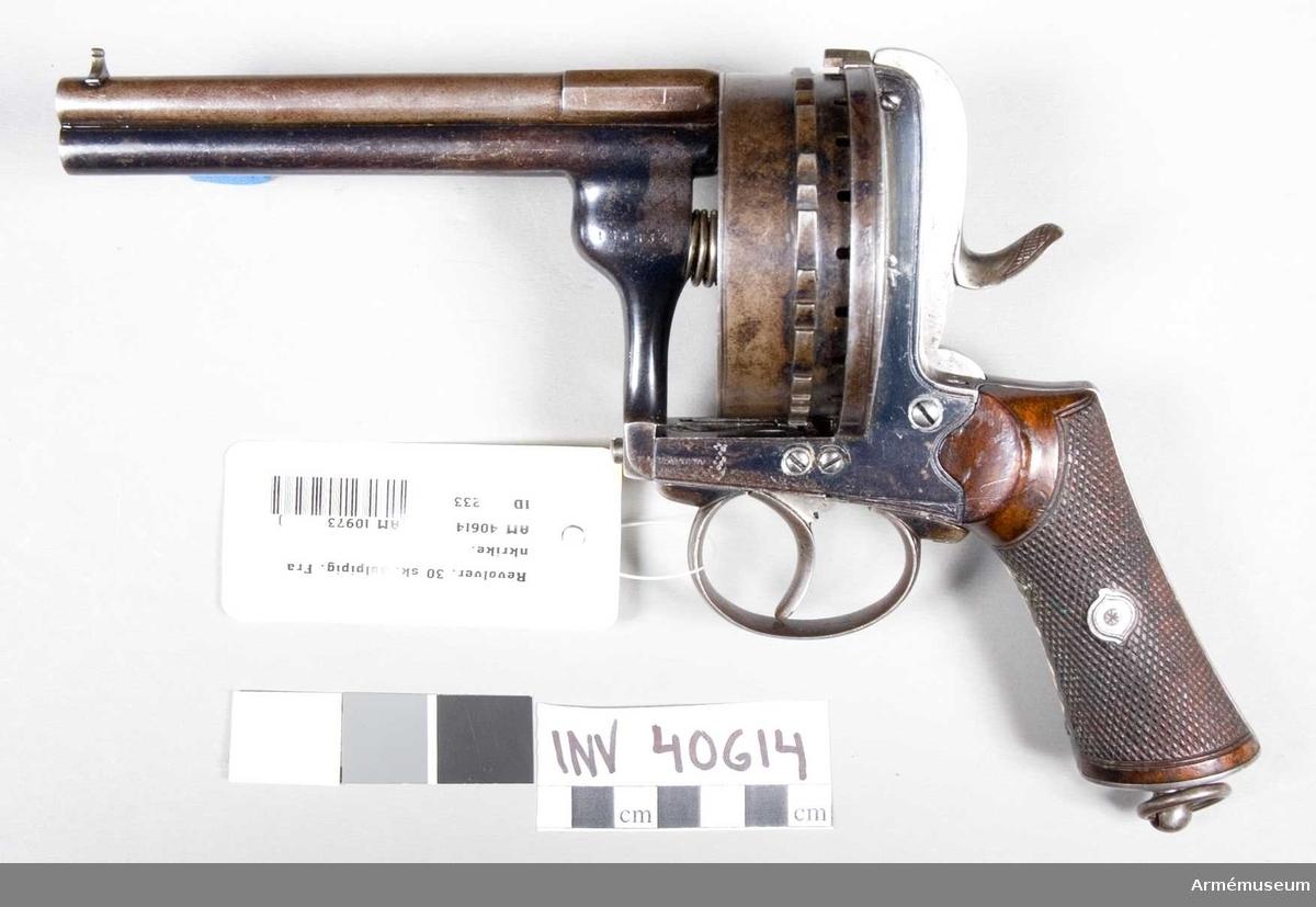 """Grupp E III. Med två pipor över varandra och patrontrumma för 30 skott. Märkt """"E.Lefaucheux Breveté. Fabr.nr. 128534"""" på framdelen av stommens vänstra del, men baktill på den övre pipans högra sida står """"905"""". Tillverkad i Belgien."""
