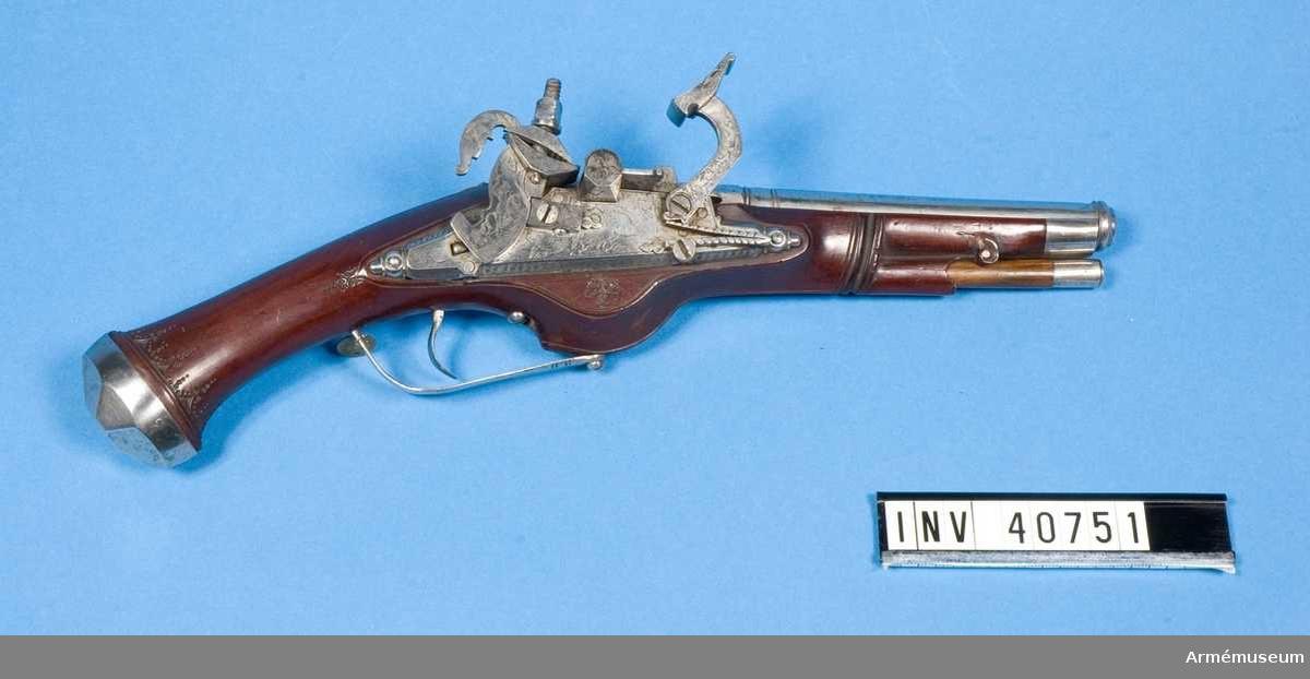 Grupp E III. Pistol med skotskt snapplås. Kontinental typ.  Vapnet är tillverkat i 1600-t början och saknar stämplar och märken. Pipan är rund med ett 6 cm långt, åttkantigt kammarstycke, samt en ringformad förstärkt trumf.   Låset är av järn, som helt täckes av etsad dekor med jaktmotiv. Det fasthålles av tre låsskruvar varav den mittre är formad som en ögla, troligen att använda som fäste för en pistolsnodd.   Stocken är av polerad mahogny med beslag av järn. Kolvkulan är spetsig och oval formad med en sjusidig fasettslipning. Sannolikt en förfalskning./1965 A Hoff.