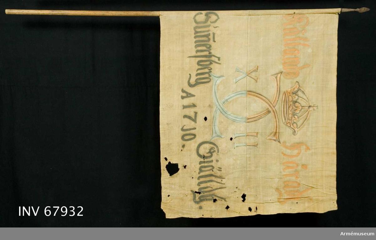 Duk: Tillverkad av enkel vit linnelärft, sydd av två horisontella våder. Vertikala fållen lagd åt dukens utsida.  Dekor: Målad endast från dukens utsida Karl XII:s namnchiffer, dubbelt C med X-II på ömse sidor, krönt med sluten krona, på det övre fältet i gult och brunt på det nedre i blått och svart. På ömse sidor text om chiffret, upptill i gult och nedtill i svart. Målning endast på dukens utsida. duken fastsydd runt stången.   Stång:  Tillverkad av trä. Spets av järn.