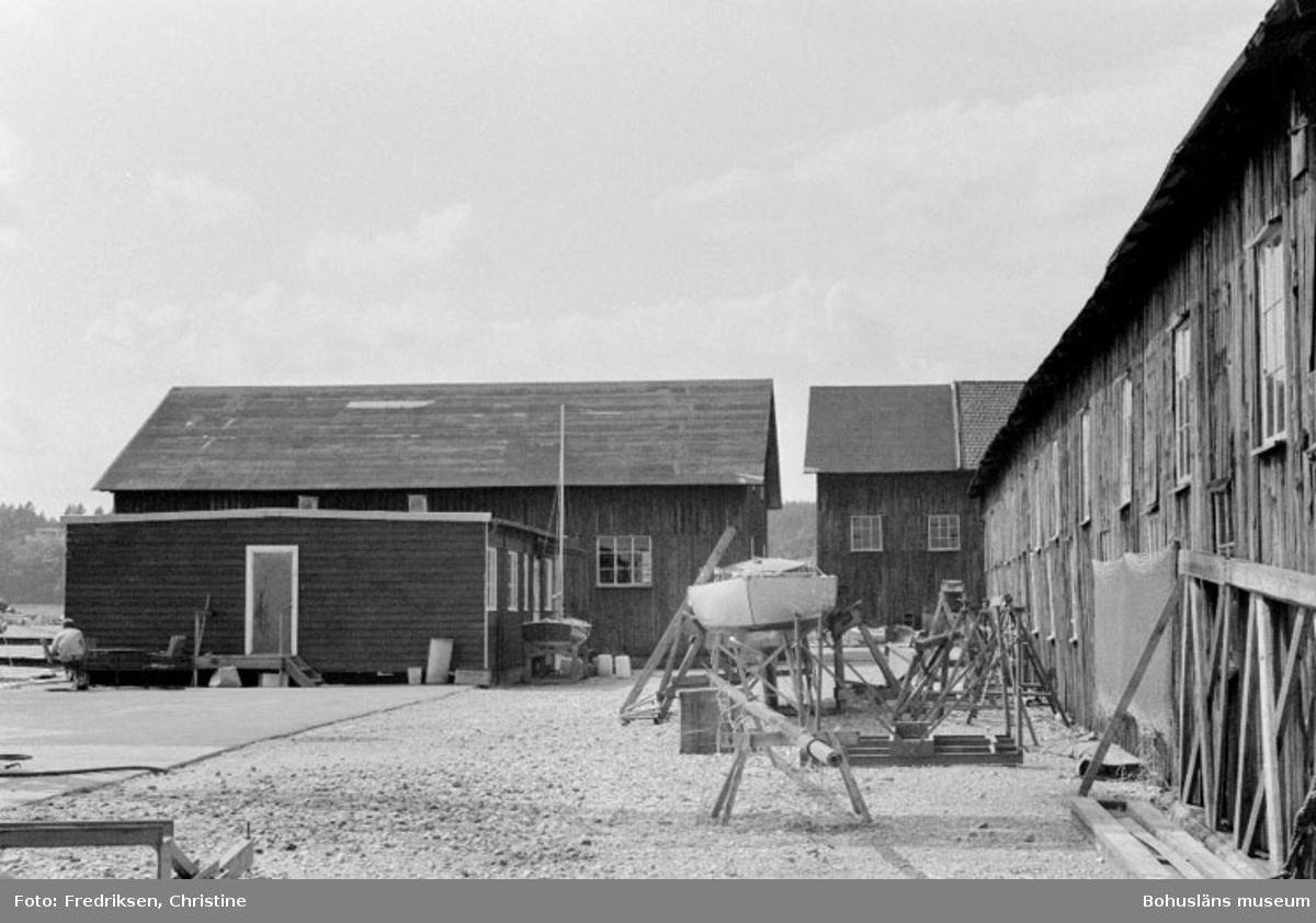 """Motivbeskrivning: """"Allmags varv, Allmag, Orust. Till höger i bild; byggnad för vinterförvaring av båtar (tidigare användning som bl.a båtbyggarverkstad, förmodligen uppförd i början av 1900-talet), där bakom annan byggnad för vinterförvaring av båtar (del av byggnad uppförd på 1920-talet). Till vänster nyare baracklänga för kontorsändamål, där bakom f.d. virkesmagasin uppförd på 1930-talet. Datum: 19800710 Riktning: V"""