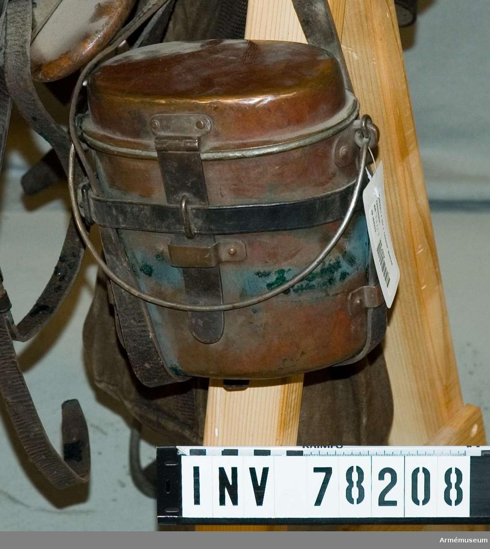 Grupp K II. Kokkärlet har en tillhörande rem för fästning vid framsnadden på sadeln och en rem som håller handtaget på locket på plats. Kokkärlet ska hänga på ryttarens högra sida. Kokkärlet saknar märkningar. 2011-10-04 MM.