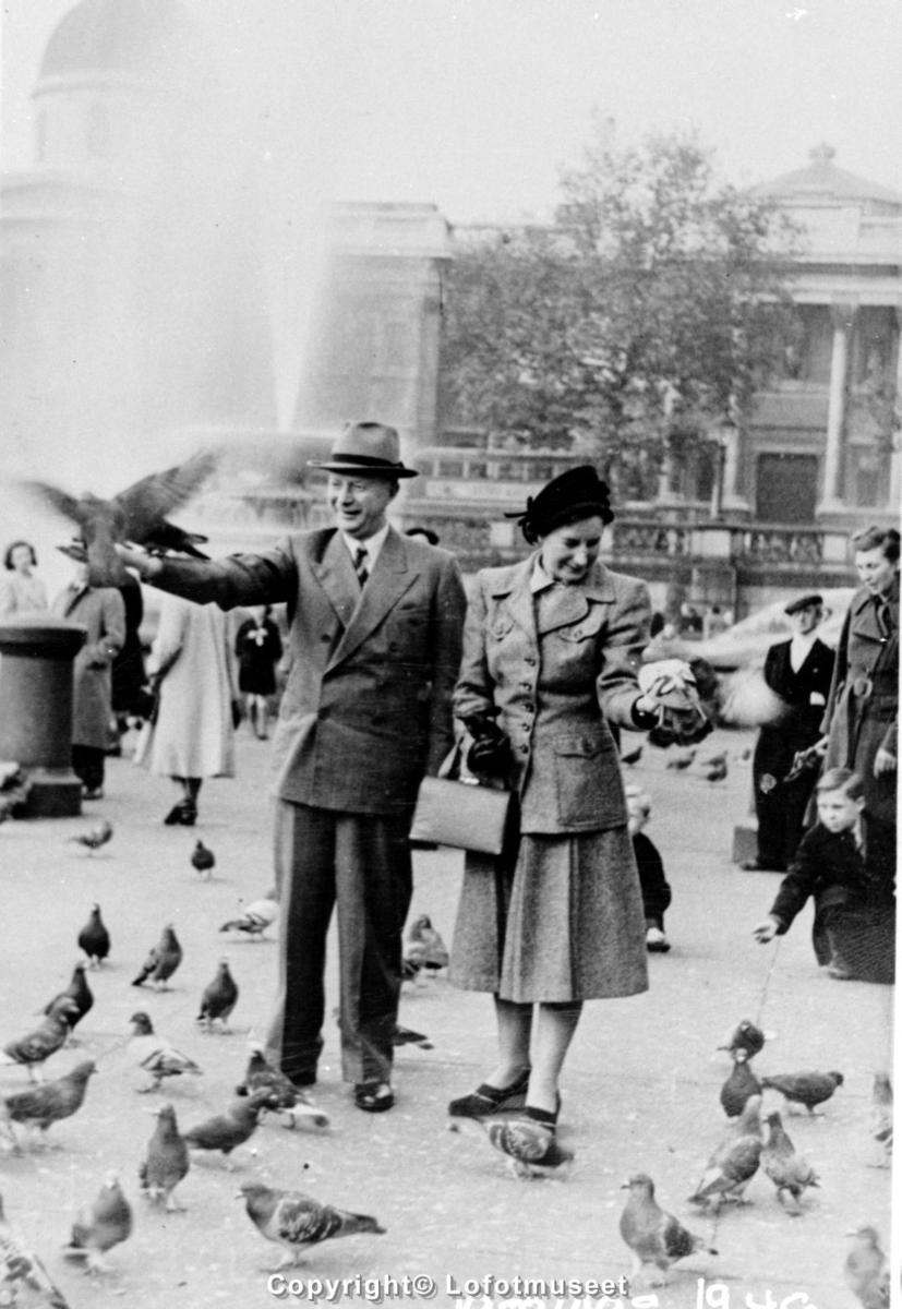 Man og kvinne mater fugler på et torg i en storby i utlandet. 1940-1950 tall