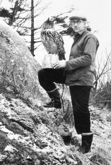 Johan Börjesson-Eld visar upp en monterad berguv ute i naturen, Stångenäs