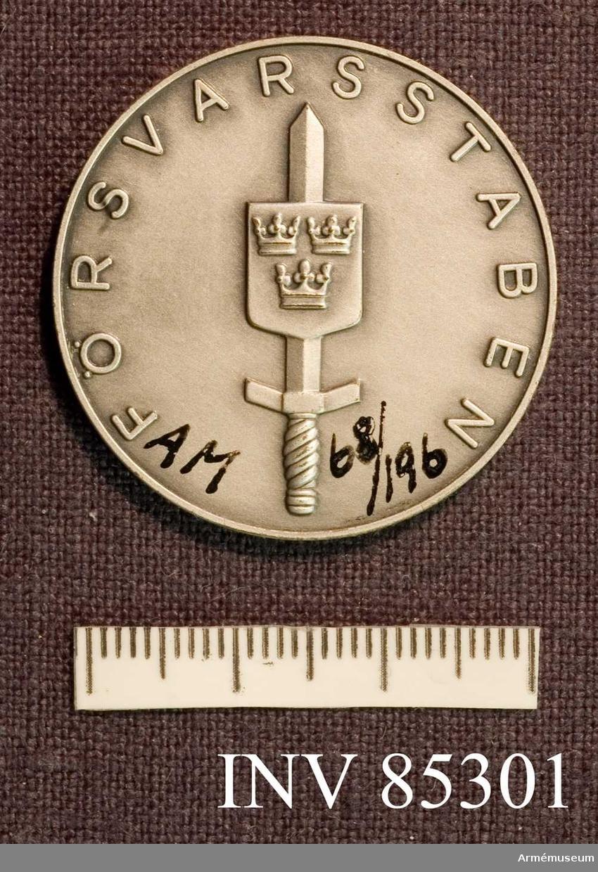 Grupp M II. För insatser till Försvarsstabens bästa. Tilldelad E. Lindgren 1964 (ej utdelad). Silver, (ej avsedd att bäras).