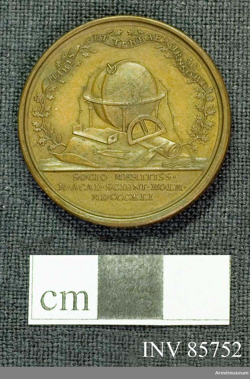 Grupp M.  Åtsidan: CP. HÄLLSTRÖM SUB CHILIARCHA EQV. AUR. Huvudet åt höger. Nedanför: M.F.  Frånsida: MARIS ET TERRAE MENSOR, på ett band, lindat om två eklövskvistar, som bilda en karans kring en grupp av instrumenter (glob, mätkedja, diopterlineal, kvadrant, cirkelmätare, penna) och kartor. I avskärningen: SOCIO MERITISS. R. ACAD. SCIENT. HOLM. MDCCCXLI.