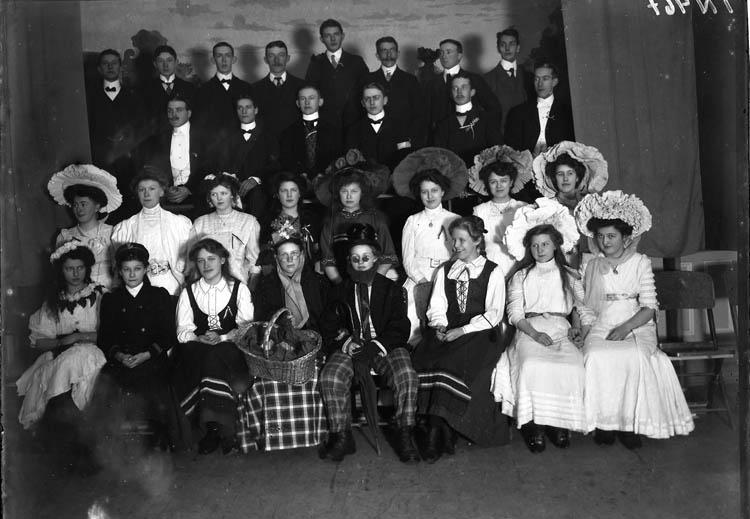 """Enligt tidigare noteringar: """"Gruppfoto av herrar och delvis utklädda damer uppställda på enkel scen. Kostymfest. Hantverksföreningen i Uddevalla."""""""