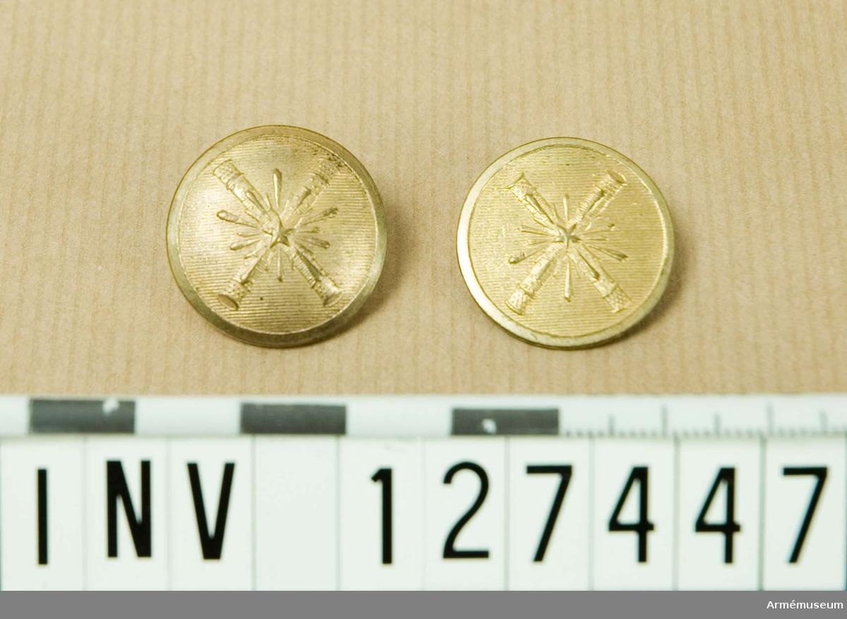 Två knappar med samma motiv. Den ena platt och den andra kullrig med baksida.