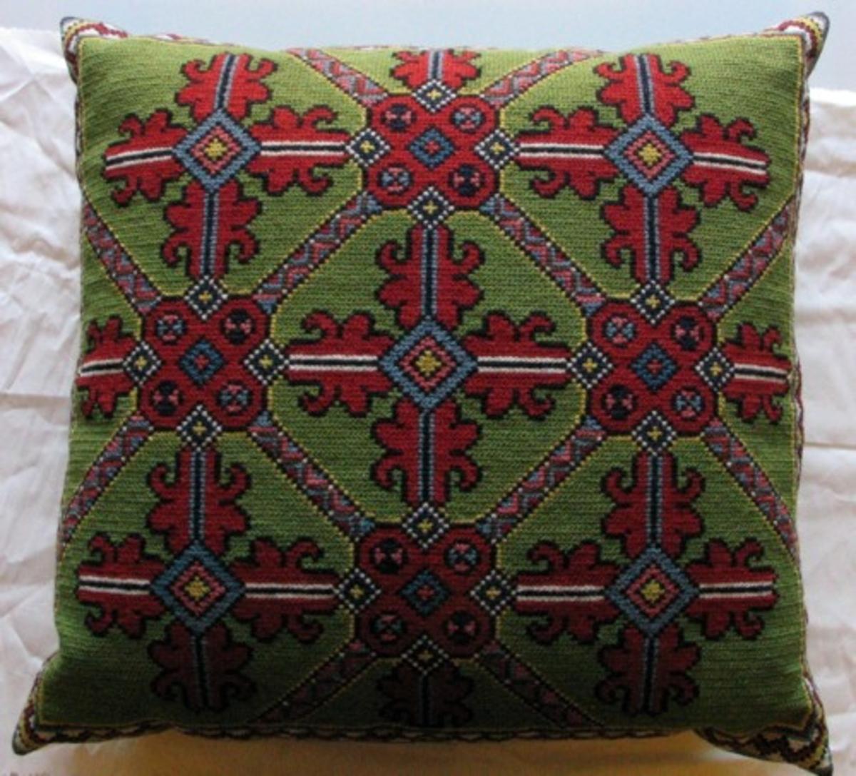 Stoppad braskudde. Broderad i tvistsöm. Klargrön botten med yttäckande broderi med mönster av röda akantusblad i ett diagonalställt rutmönster. Bård i zick-zack mönster.