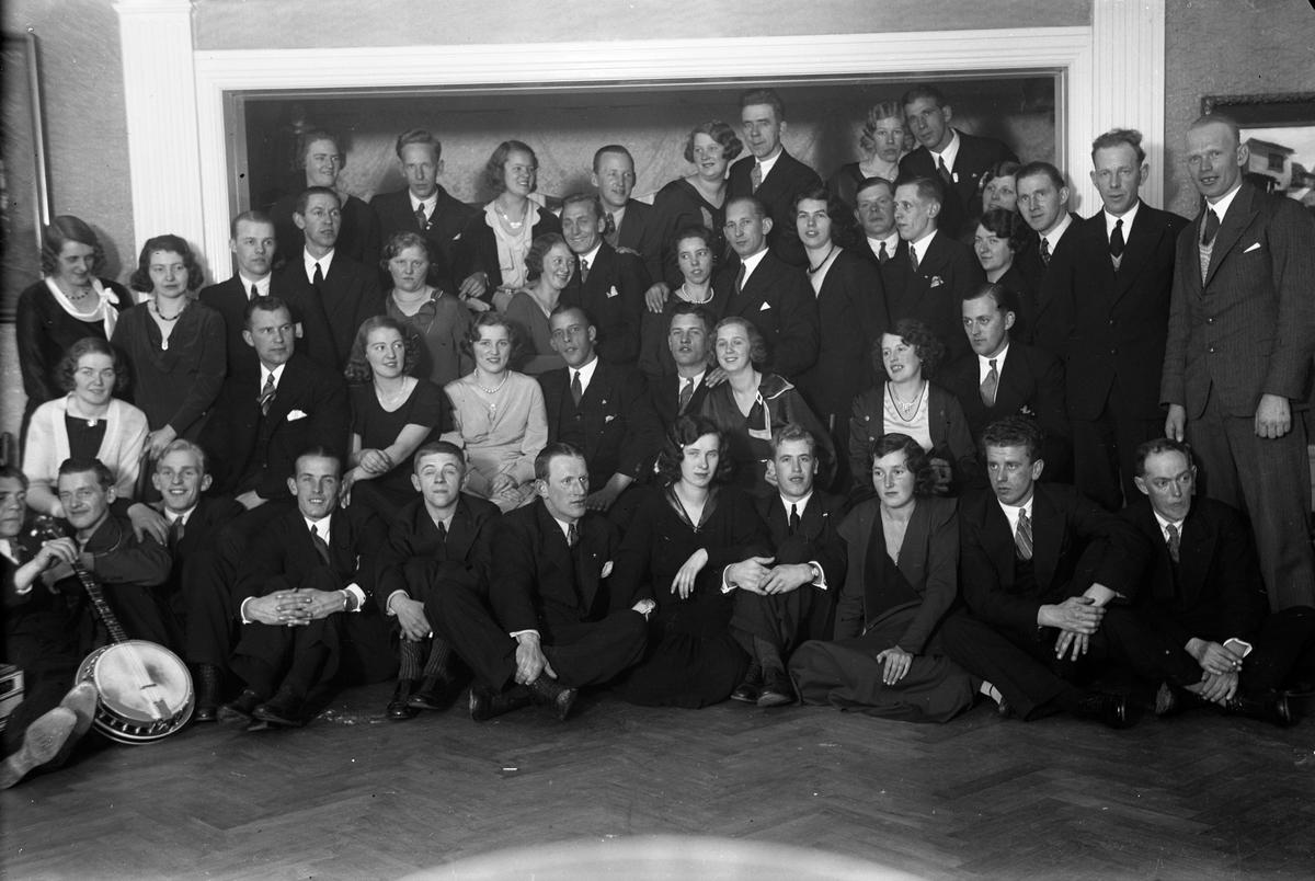 En gruppbild på män och kvinnor i en samlingslokal.