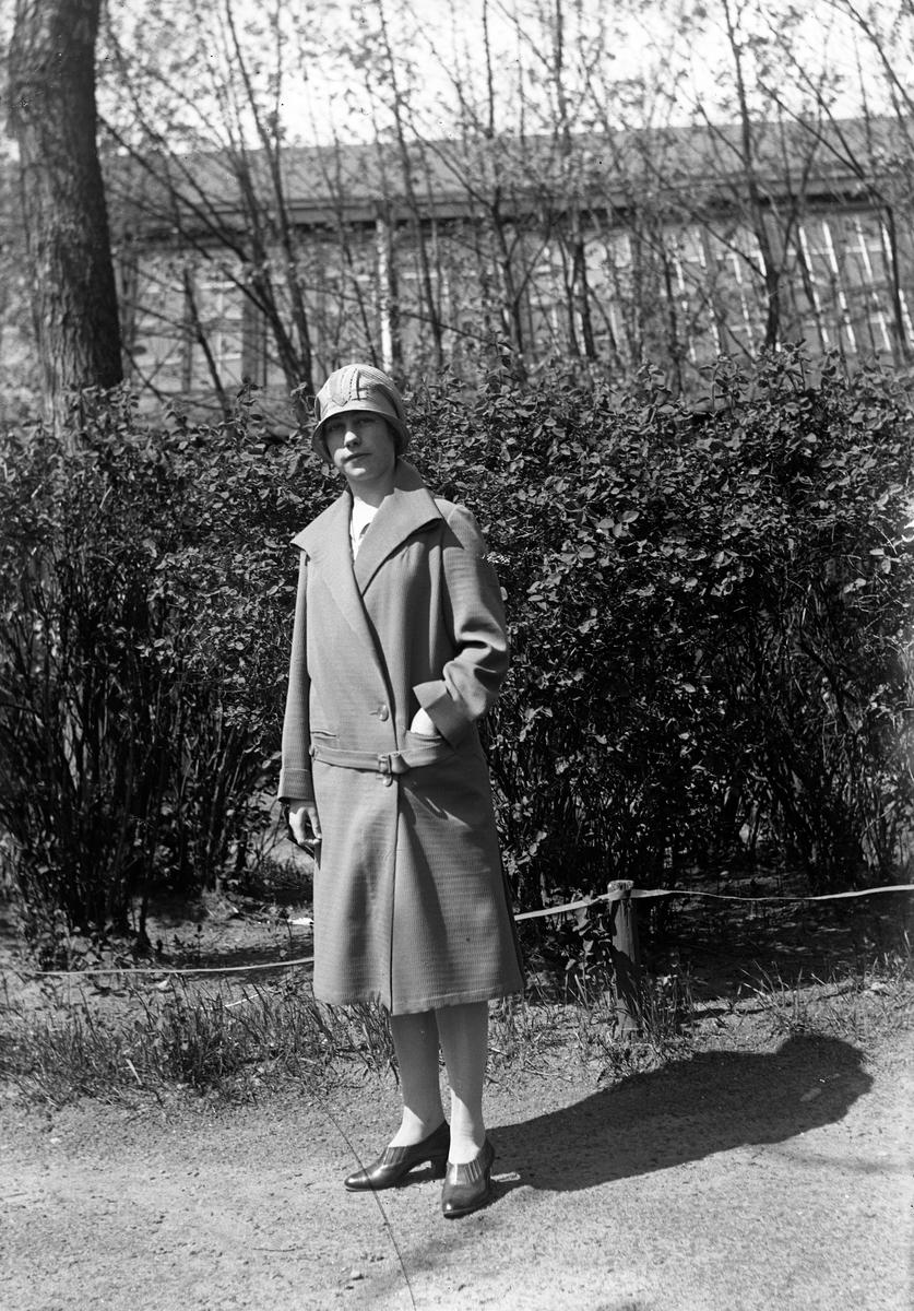 En kvinna klädd i kappa och hatt står på en väg framför en häck. I bakgrunden skymtar ett stort hus.