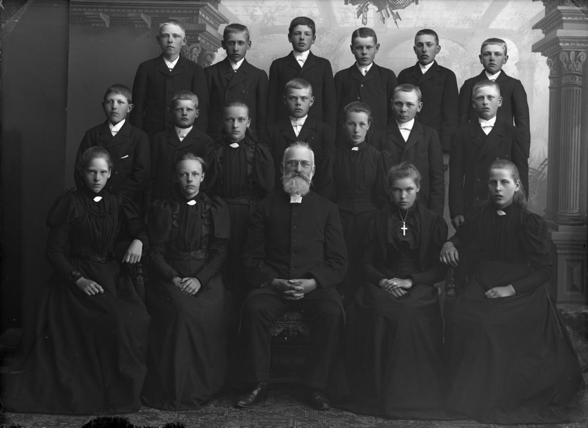 Konfirmandgrupp sannolikt från Sparrsätra, Uppland. I mitten kyrkoherde Anders Johan Norberg (1843-1914).
