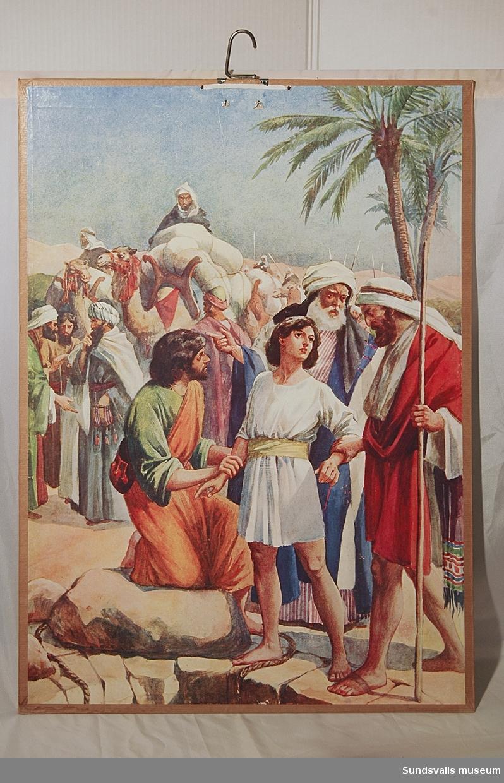 Skolplansch. Den tryckta bilden är uppfodrad på kartong med en metallkrok som upphängningsanordning i övre kanten. En etikett på baksidans nedre vänstra sida har texten 'SAIETZ Nelson: Gamla Testamentet Josef säljes av sina bröder 106'.