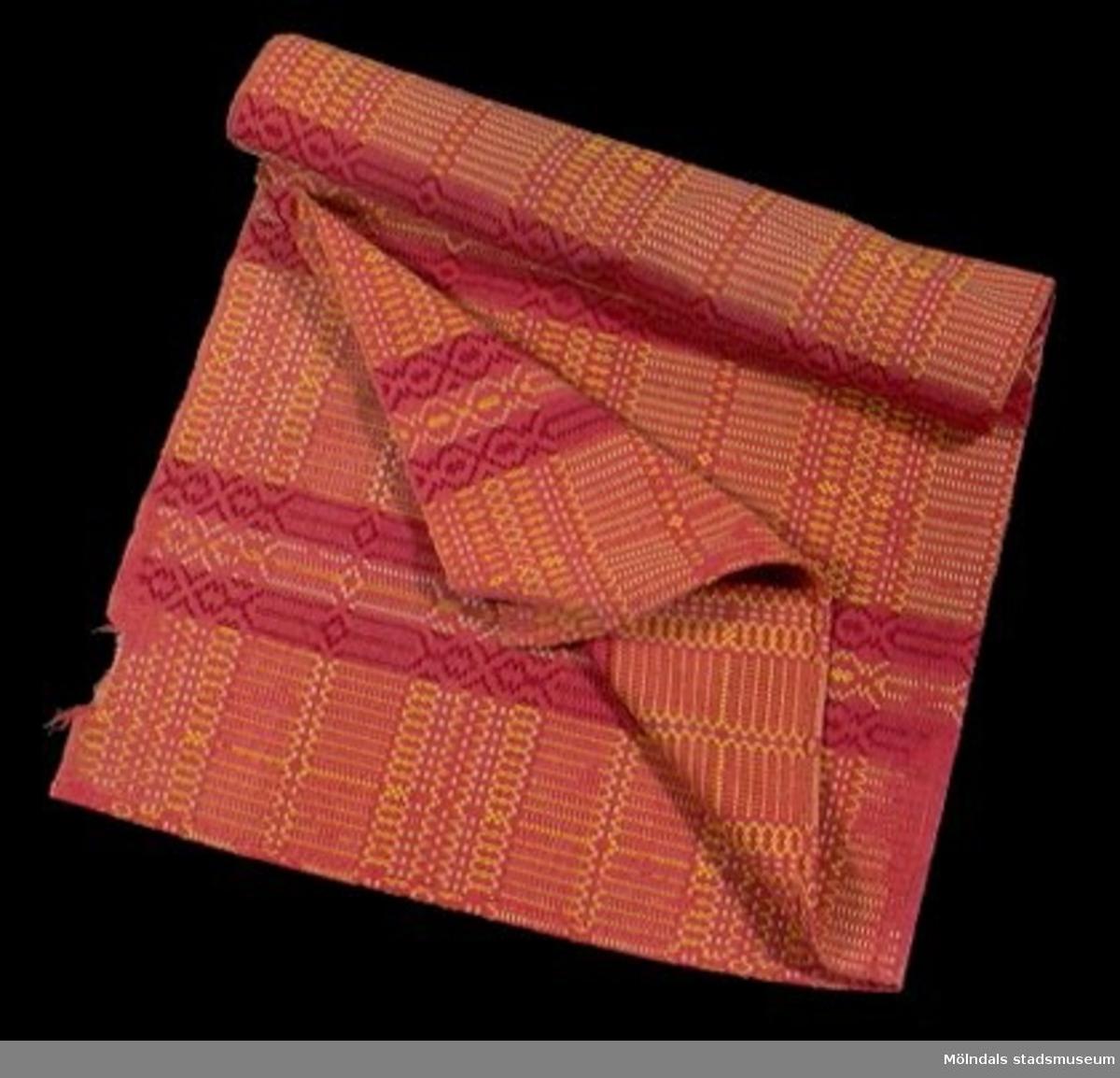 Vävt i två stycken, ihopsydda. Röd botten med gult och rött mönster. Tuskaft. Bottenväv lingarn, mönsterinslag ullgarn.