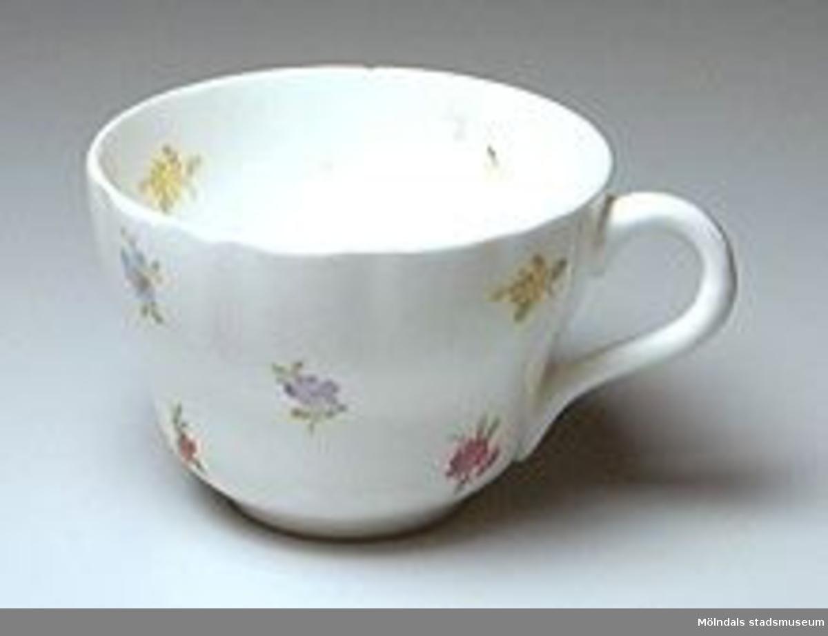 """Kaffekopp (utan fat) med """"päronform"""". Vit med små röda, gula och blå blommor som dekor. Öppet öra."""