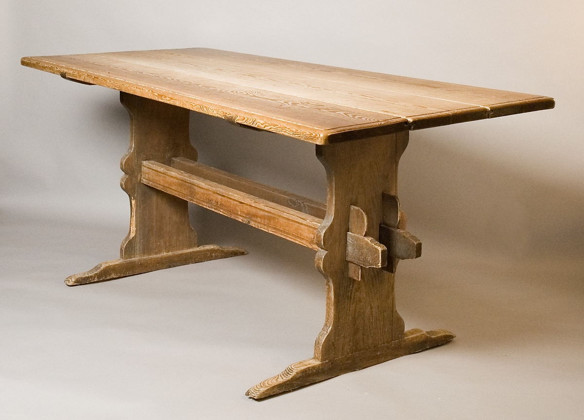 """Bockbord av trä. Skiva av tre nåtade bräder, med en avfasad rundad kant på ovansidan, 24 mm (1"""") bred. Raka ben med tvärställda fötter, rundade dekorsågningar vid mitten. Dubbla tvärslåar, med urfräsning upptill och på yttersidorna. Kilar med rundade hörn."""