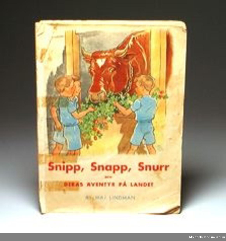 """Titel: """"Snipp, Snapp, Snurr och deras äventyr på landet"""" av Maj Lindman.Märkning på försättsbladet."""
