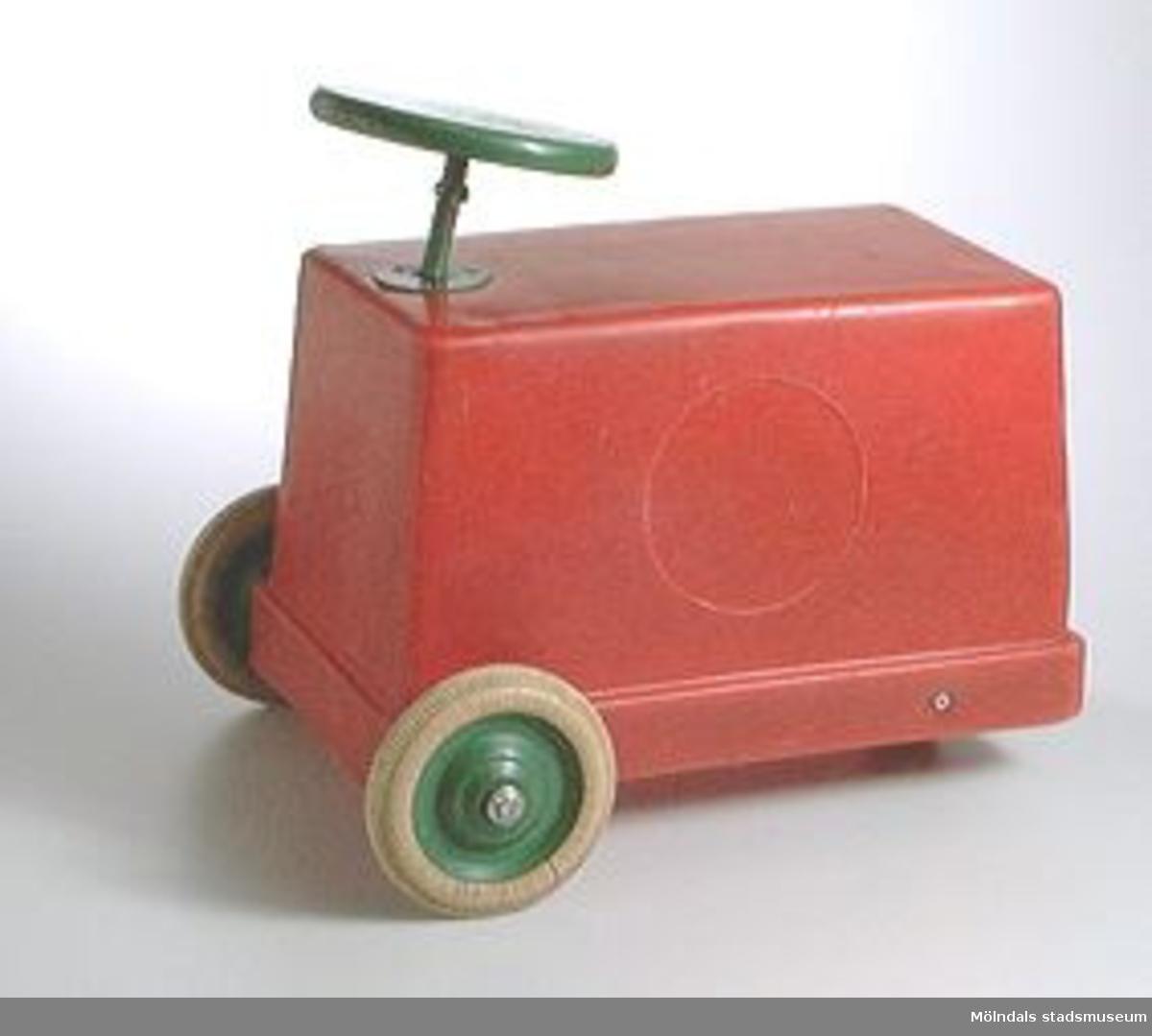Röd åkbar leksaksbil i röd plast. Svartmålad träratt och gummihjul.