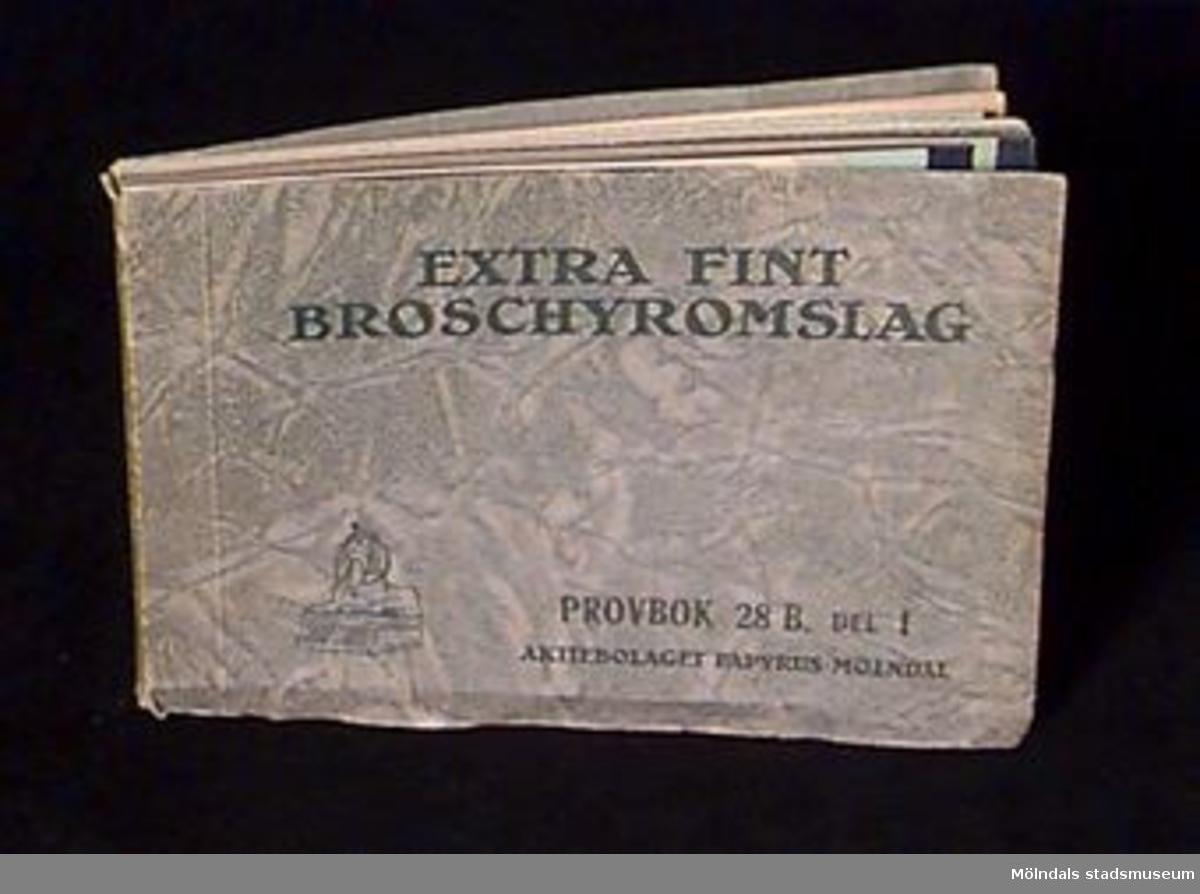 """Bokens omslag har en gråmarmorerad yta. Med mörkgrå tryckta bokstäver står """" Extra fint broschyromslag"""". Papyrus logotype med sfinxen är märkt i nedre vänster hörn.Varje provblad är märkt med en siffra. Bokens pärm är något skadad, stött i kanter och hörn, samt lite trasig i ryggens över och nederdel.Litteratur: Papyrus 1895-1945, Minneskrift, Esseltes Göteborgsindustrier AB, Göteborg 1945."""