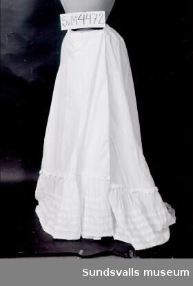 Underkjol i vitt linne. Vid modell med dragsko i midjan. I nederkanten är en 34 cm bred volang med fem platta veck påsydd. Taggig kant.