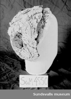 Svart hårklädsel med beige blommönstrad spets i lager och lila fuskpäls. Oval form.